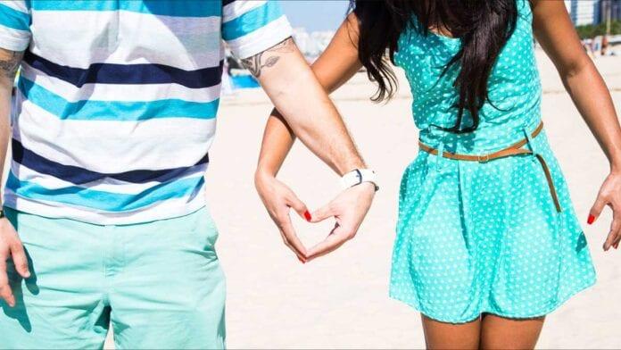 couple holding heart-shaped hand on beach