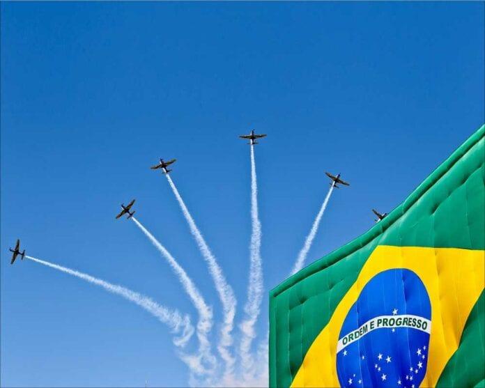 Aerobatic planes soar above brazilian flag