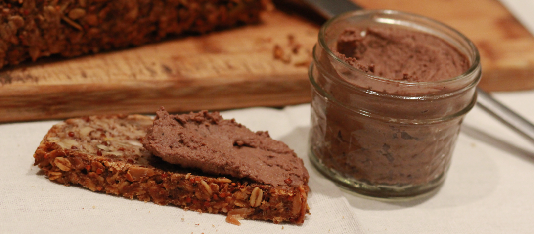 a jar of pate and pate spread on a pice of bread
