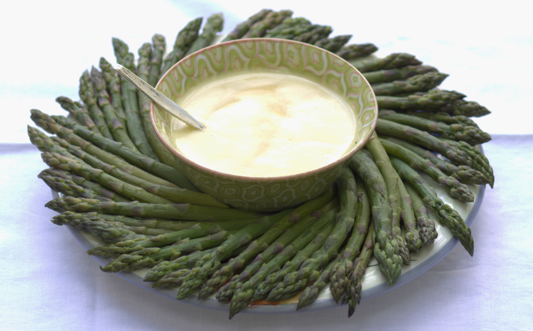 asparagus arranged in a circle with a bowl of sauce in the middle