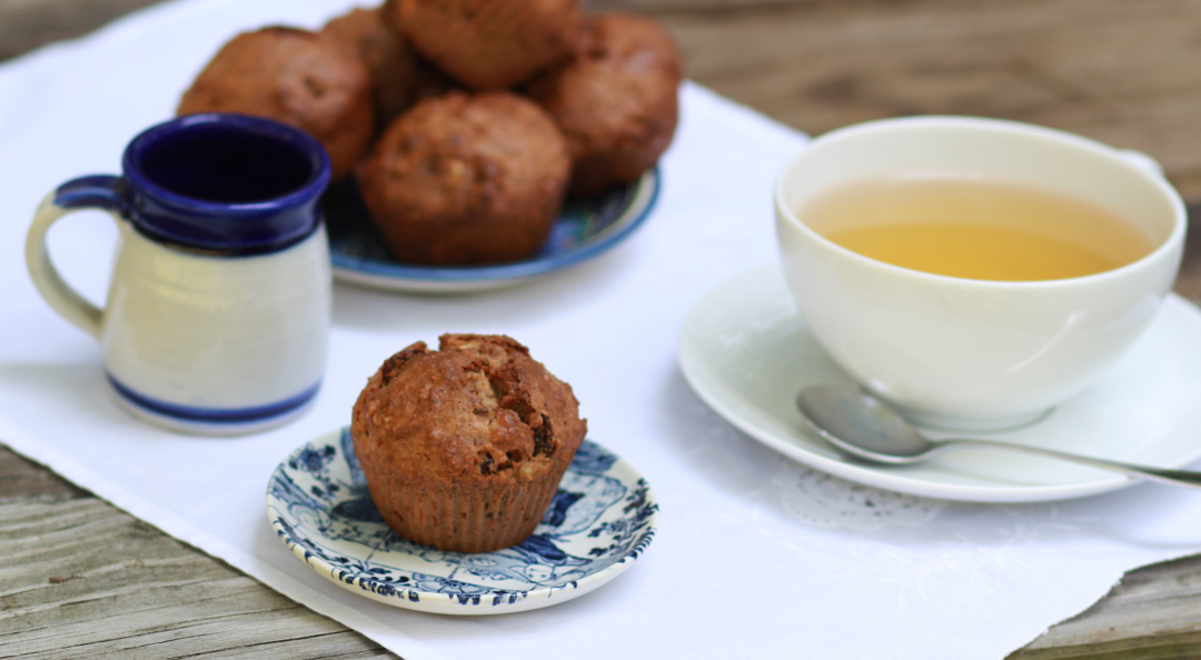 Rustic muffins on a little plate, a cup of tea, a jar of milk and more muffins on the background