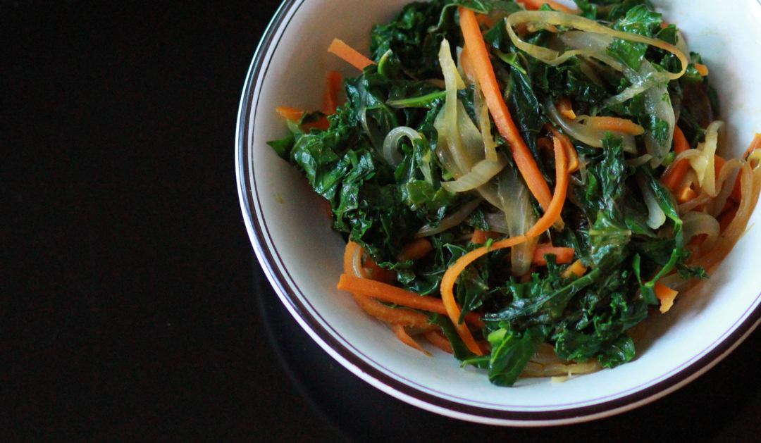 a bowl with kale and carrot sauté on black background