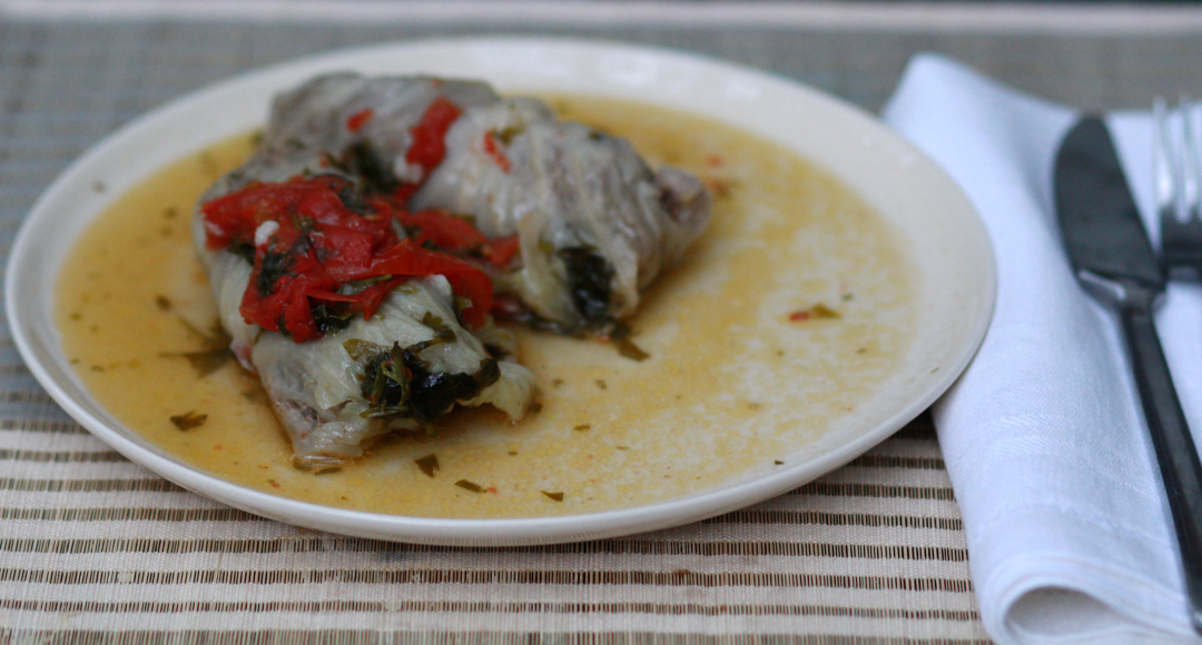 two stuffed cabbage leaves on a plate