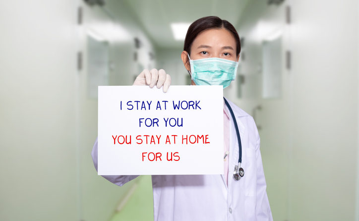 Doctor at hospital wearing mask, holding sign that says I STAY AT WORK FOR YOU, YOU STAY AT HOME FOR US