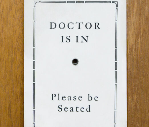 A doctor is in sign hung on a door