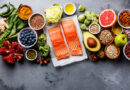 Fish surrounded by vegetables, fruit, nuts, and other healthy food choices