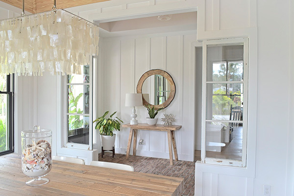 farmhouse dining room, entryway, capiz chandelier, west elm, table, white lamp, round wood mirror, seashells, beach cottage, white walls, board and batten
