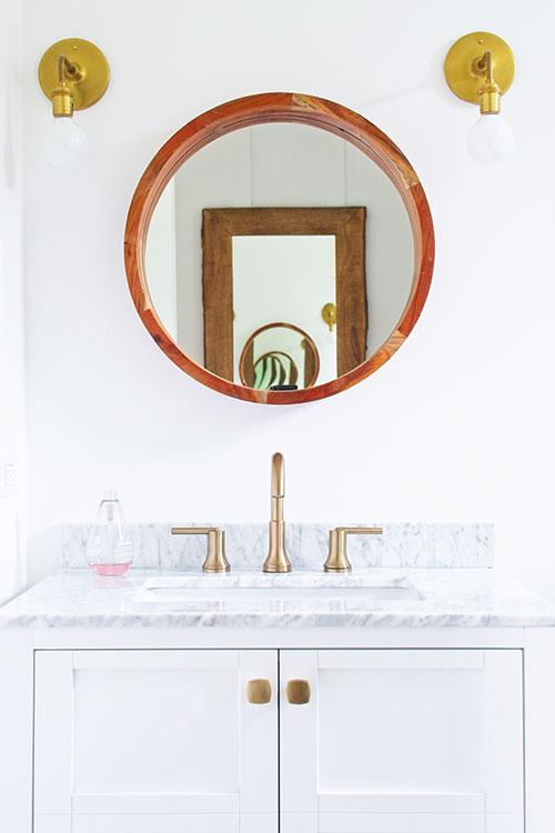 farmhouse bathroom round wood mirror brass wall sconce gold brass faucet hardware bath vanity