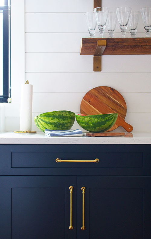 farmhouse kitchen navy blue cabinets brass hardware open shelving watermelon cutting board paper towel holder