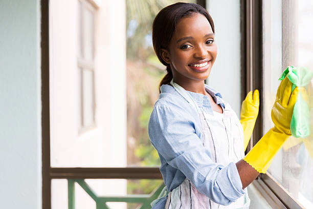 attractive african girl cleaning window glass