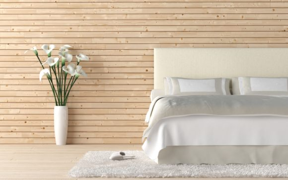 Interior design of wooden bedroom with bed and a vas of calla lilly flowers