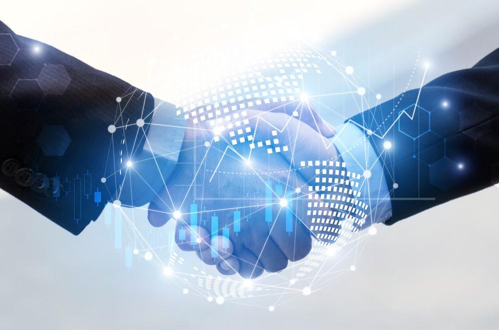 Businessman shaking digital partners hand on blue background