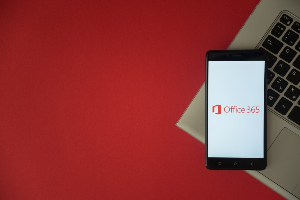 London, United Kingdom, October 23, 2017 Microsoft office 365 logo on smartphone screen placed on laptop keyboard. Empty place to write information with red background.