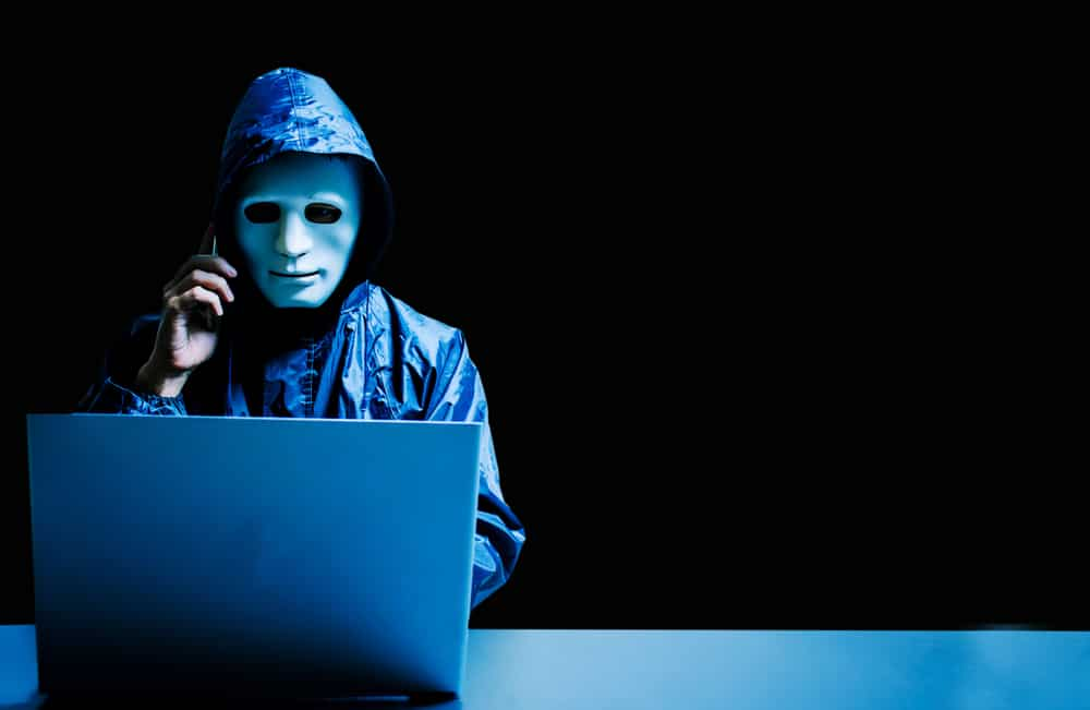 Anonymous computer hacker in white mask and hoodie