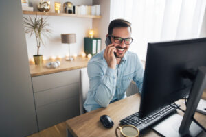 Smiling handsome freelancer working remotely from home. He is speaking on the phone.