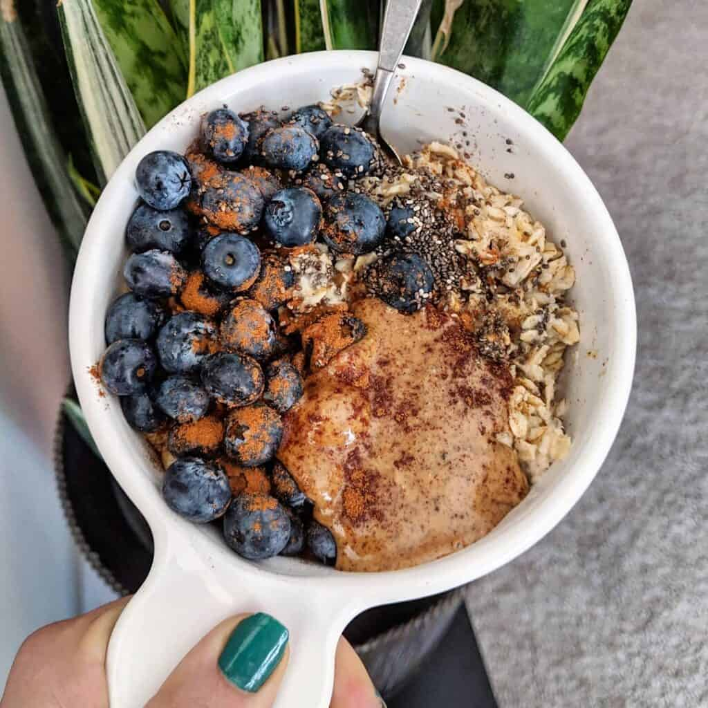 Cooked oatmeal topped with berries, nut butter, and seeds