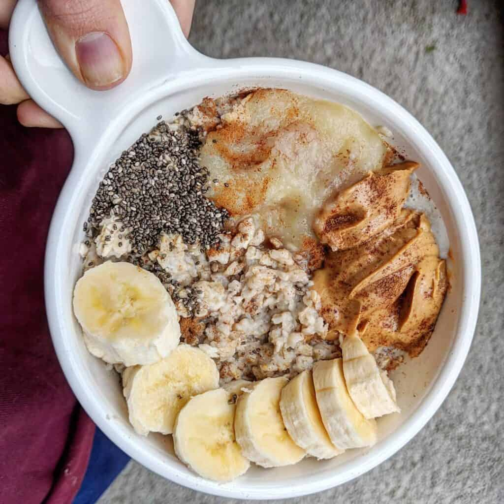 Cooked oatmeal topped with banana, nut butter, chia seeds and applesauce. An easy healthy breakfast