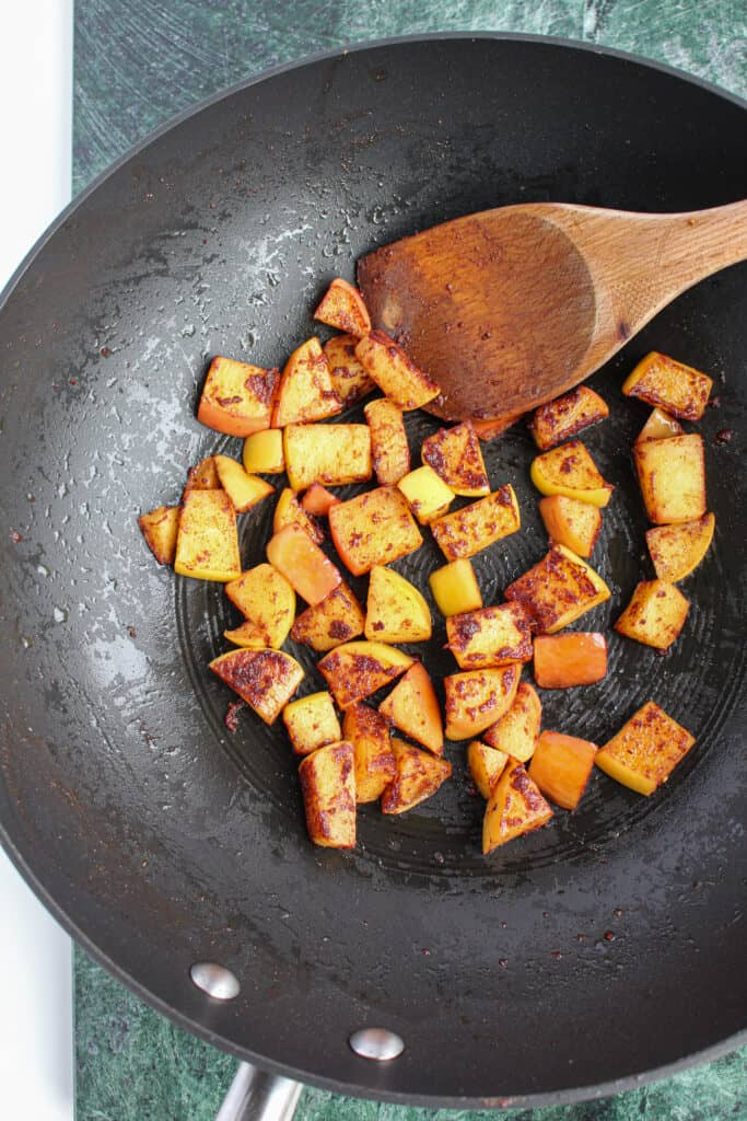 Apples sauteed in coconut oil in a black wok with a wooden spoon.