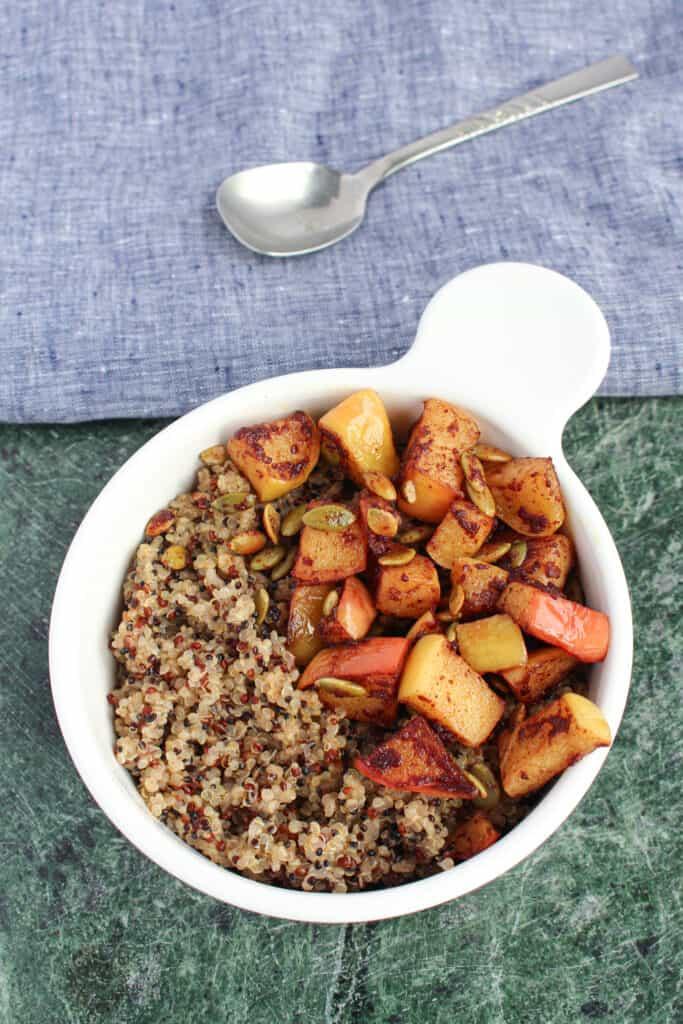 A bowl of coconut milk breakfast quinoa on a green granite cutting board