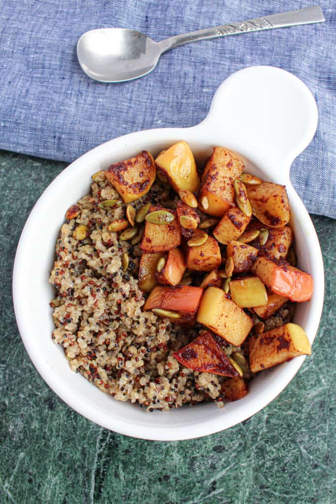 White bowl with cooked quinoa, sauteed apples, and toasted pepitas on a green granite cutting board. Blue cloth with spoon in the background.