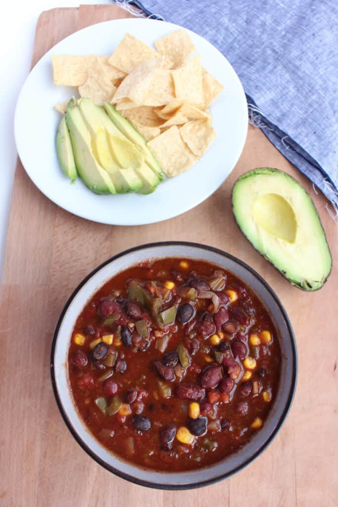 Bowl of chili with avocado and tortilla chips. A nutritious gluten free, vegan meal.
