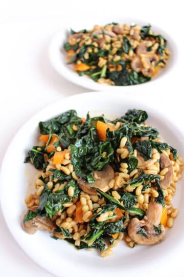 A grain and vegetable salad served on 2 white plates. The salad is comprised of cooked kamut, sauteed kale, orange bell pepper, and sliced mushrooms