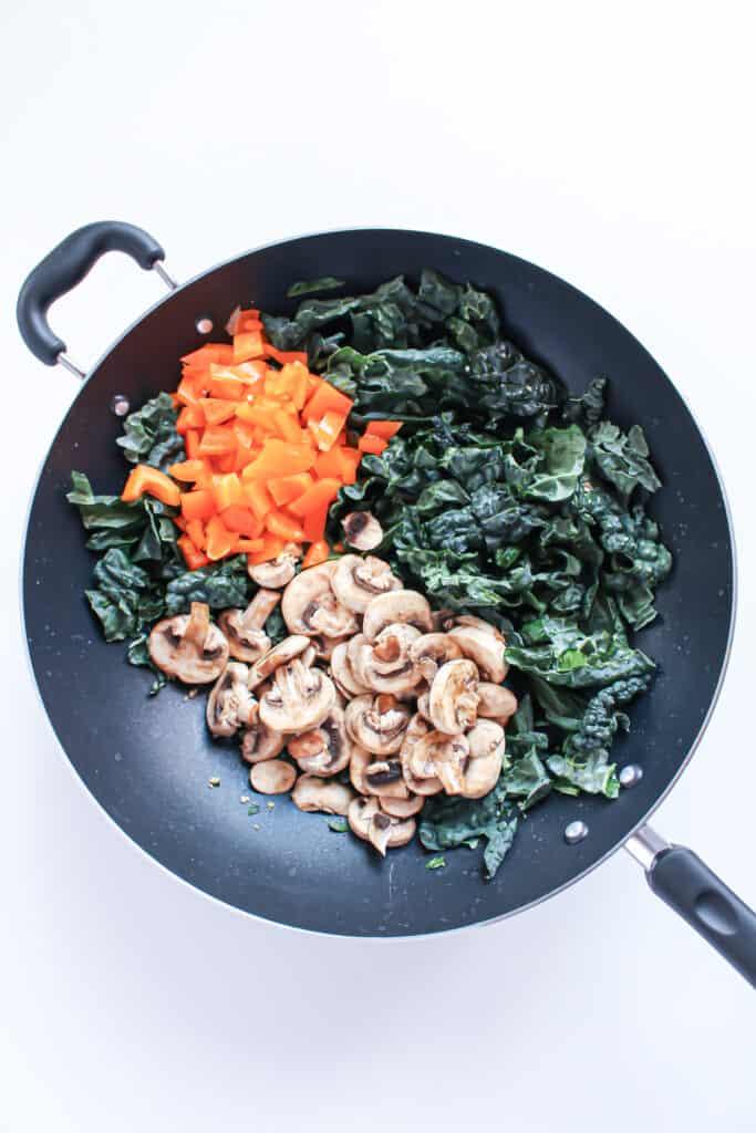 Chopped orange bell pepper, kale and sliced mushrooms in a black wok