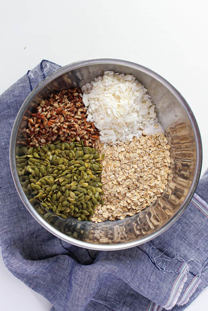 An aerial shot of a mixing bowl with the dry ingredients: pumpkin seeds, shredded coconut, oats, and pecan pieces.