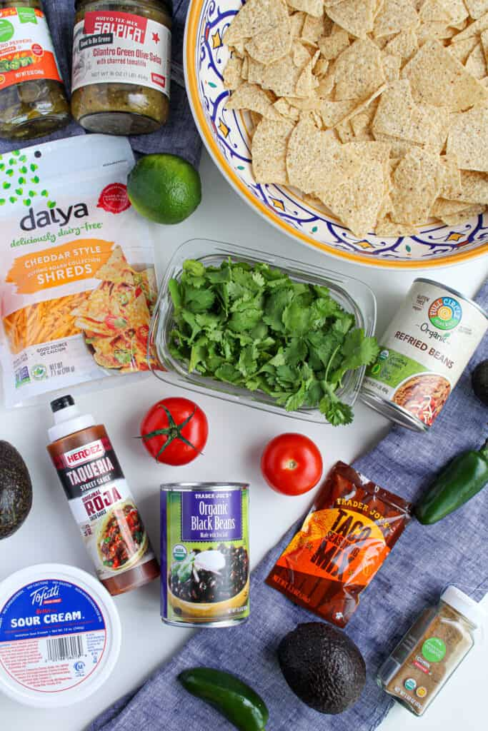Ingredients to make vegan nachos: a whole jalapeno pepper, avocado, tomato, jar of cumin, container of tofutti sour cream, can of black beans and refried beans,, hot sauce, jar of salsa, tortilla chips served in a bowl, vegan daiya cheese.