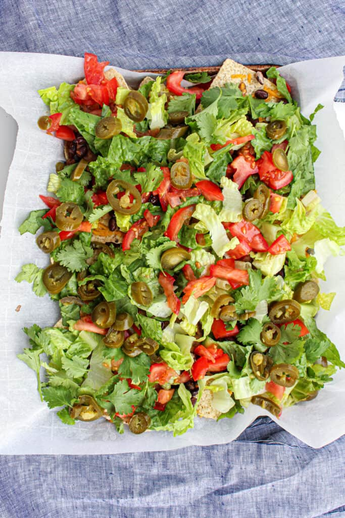 above view of a sheet pan of nachos covered with lettuce, pickled jalapeno, and tomatoes