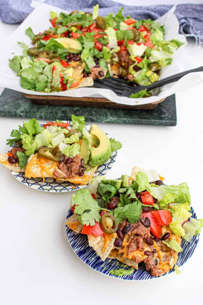 Two small white and blue plates with nachos plated. Sheet pan in the background with spatula