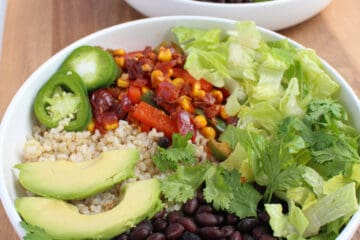 Two white bowls filled with rice, black beans, fiesta vegetables, lettuce, cilantro and pickled jalapeno on a wooden background