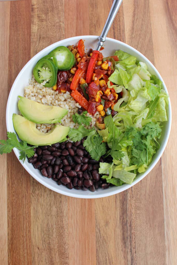 A single vegan black bean burrito bowl. One white bowl on wooden background with black beans, brown rice, lettuce, cilantro, avocado, fiesta veggies, and pickled jalapeno. Served with a fork