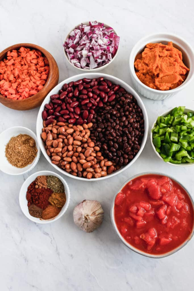 Individual ingredients to make vegan pumpkin chili (tomatoes, red onion, green bell pepper, beans, carrots, pureed pumpkin, herbs and spice) all in separate bowls with a bulb of garlic on a marble background.