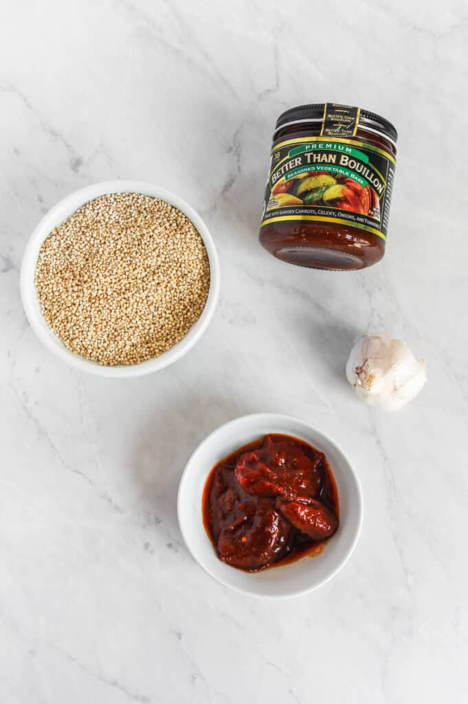 Four of the ingredients needed for this recipe on a marble background: Bowl of dry quinoa in a white bowl, head of garlic, chipotle peppers in a white bowl, and better than bouillon jar.