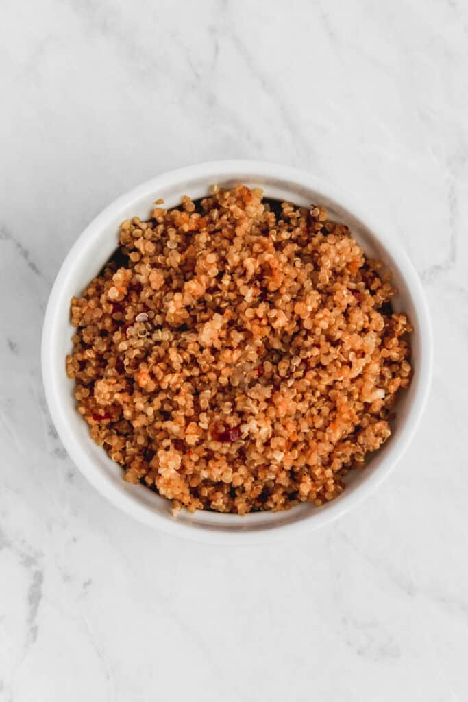 Garlic chipotle quinoa served in a white dish on a marble background