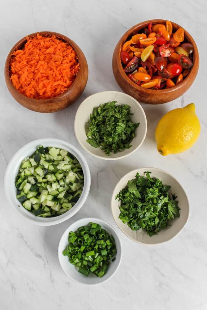 Six separate bowls of individual ingredients: chopped parsley, mint, green onion tops, cucumber, shredded carrot, and quartered cherry tomatoes and a whole lemon on a marble background