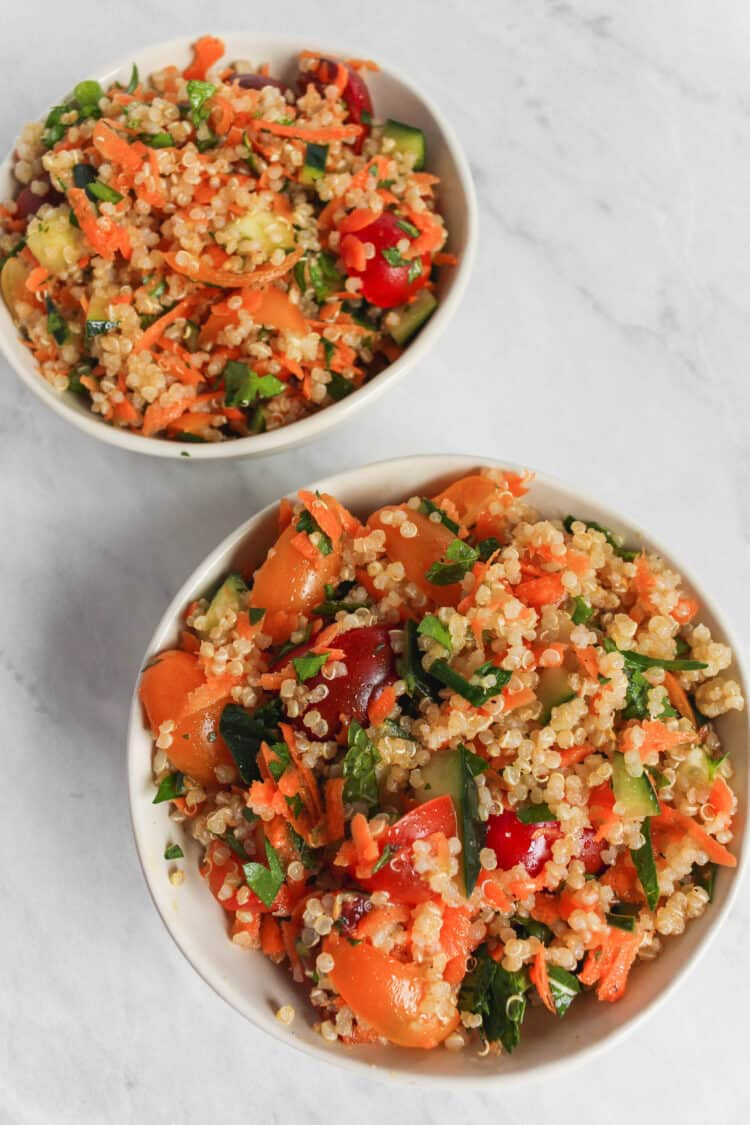 Two serving bowls filled with the quinoa tabbouleh salad on a marble background