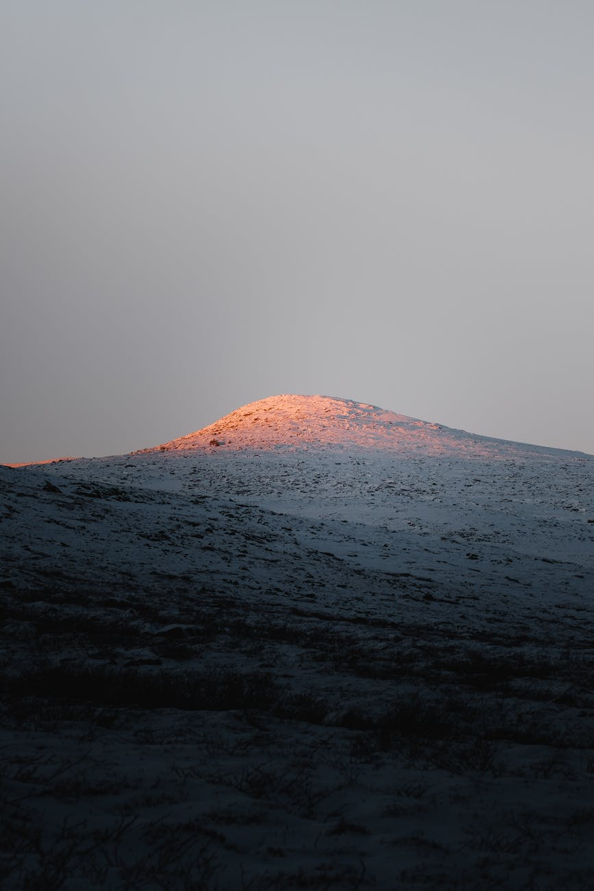 top of snowy mountain illuminated by sunlight
