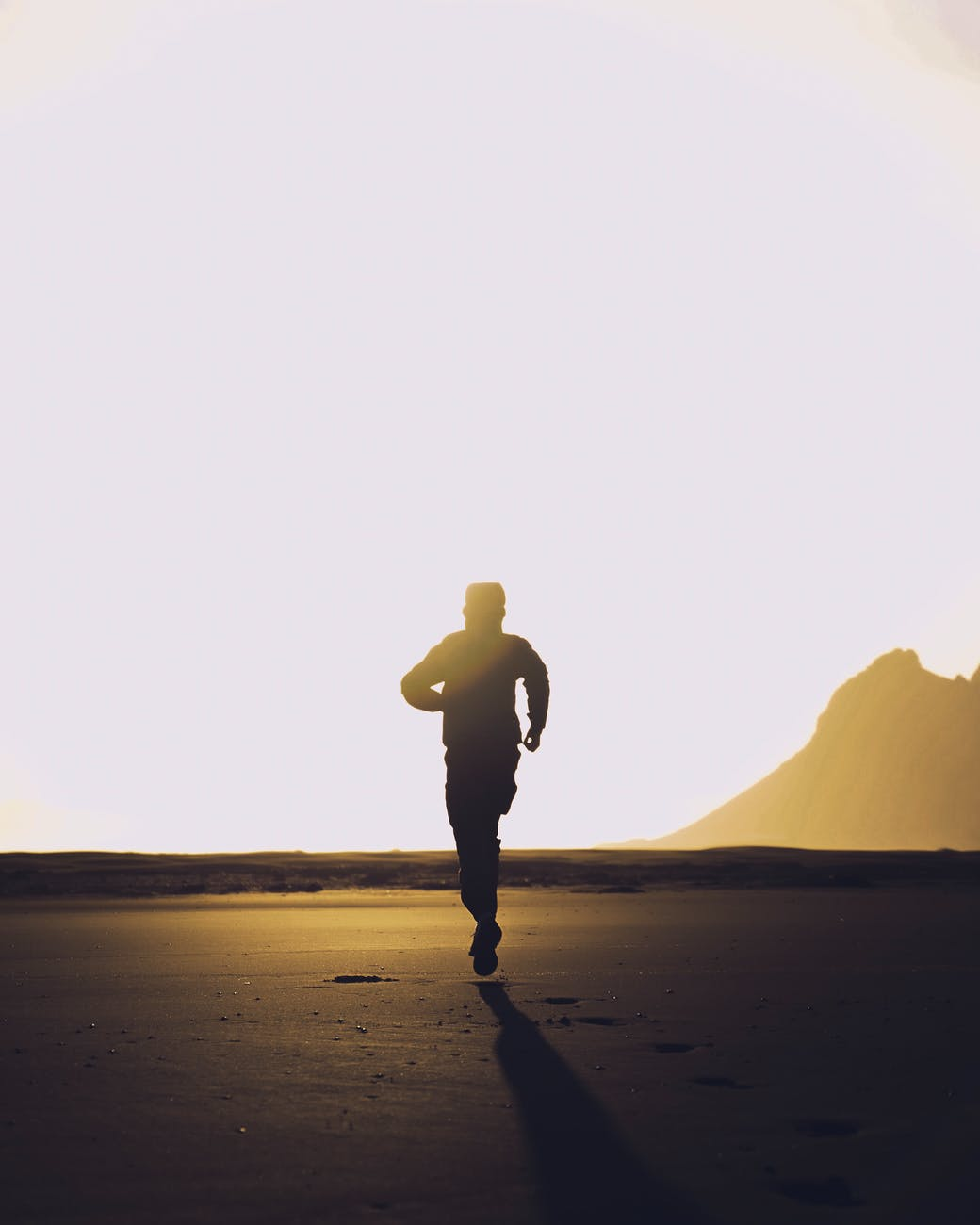 silhouette of unrecognizable man running on sand at sunset