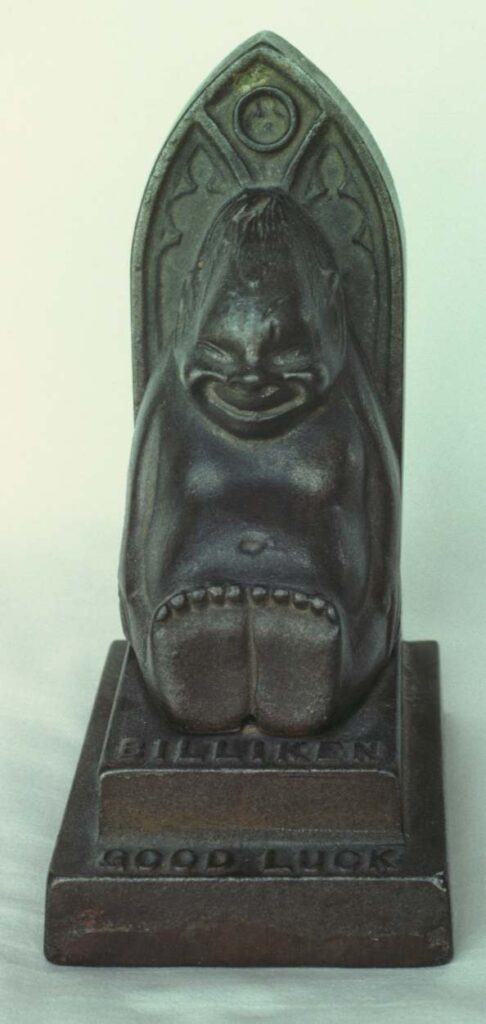 Cast iron bank, six and a half inches high overall. The billiken is four inches high. Made in 1908.