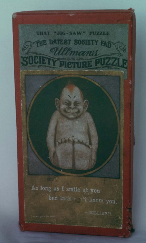 Cover of box for billiken puzzle. Cardboard. 1908
