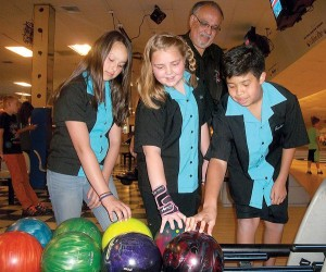 West Valley Bowl Junior Travel League coach Bill Moreno looks on as Emily Isola, 12, Abbigail Hickman, 10, and Jaeden Mah-Bishop, 13, pick out their bowling balls to practice for the 2014 California Pepsi USBC Youth Championship State Finals, which they will compete in this weekend in Southern California. Anne Marie Fuller/For the Tracy Press