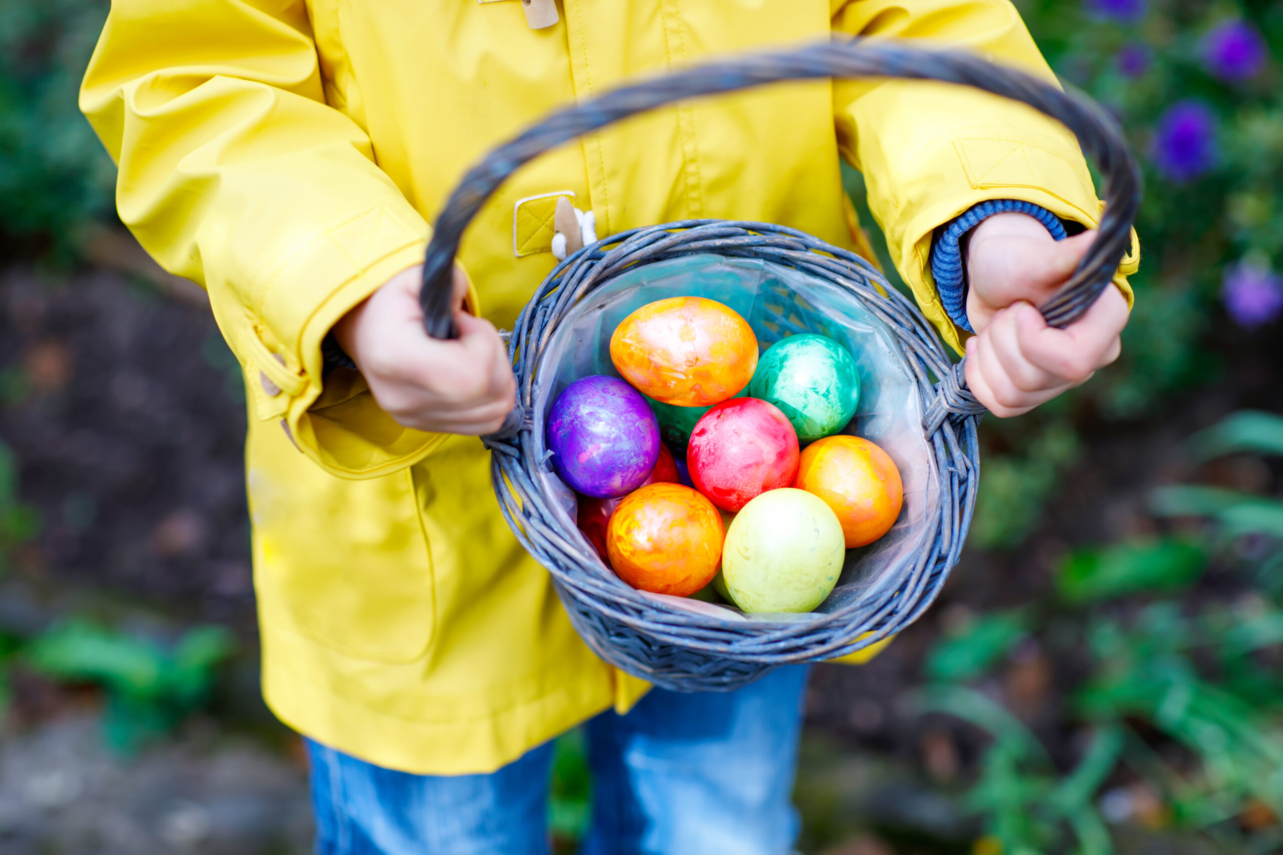 Child Holding Basket Of Easter Eggs