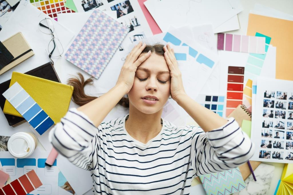 Above view portrait of exhausted young woman  lying on top of art and design supplies, copy space