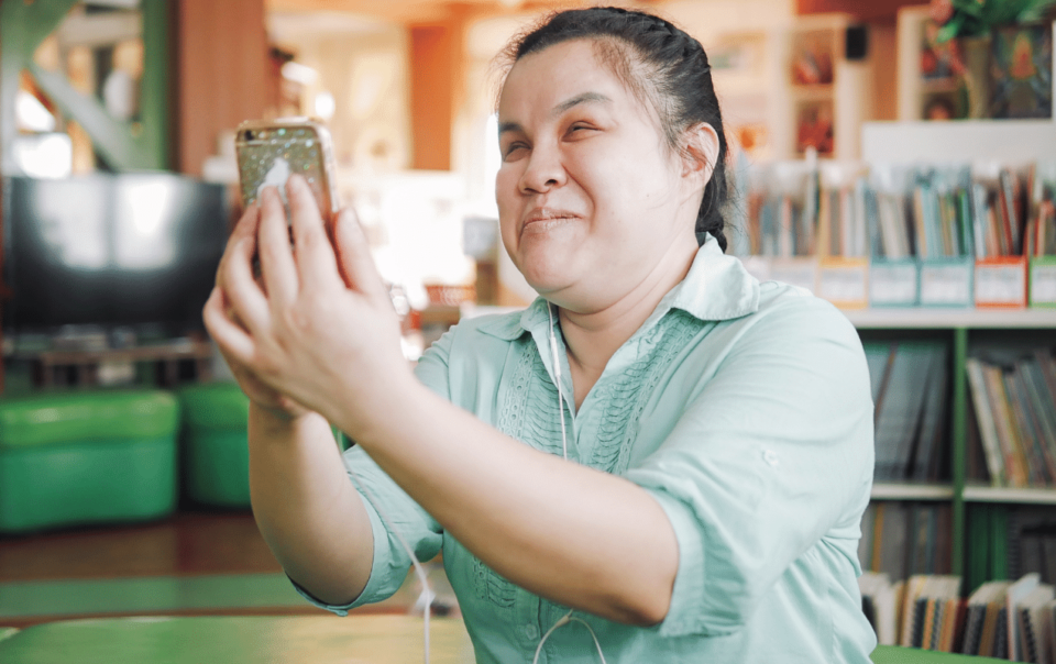Young woman with visual impairment looks at cell phone.