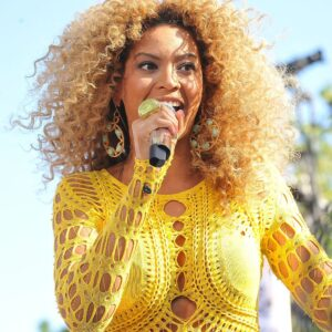Beyonce holding a microphone wearing a yellow top