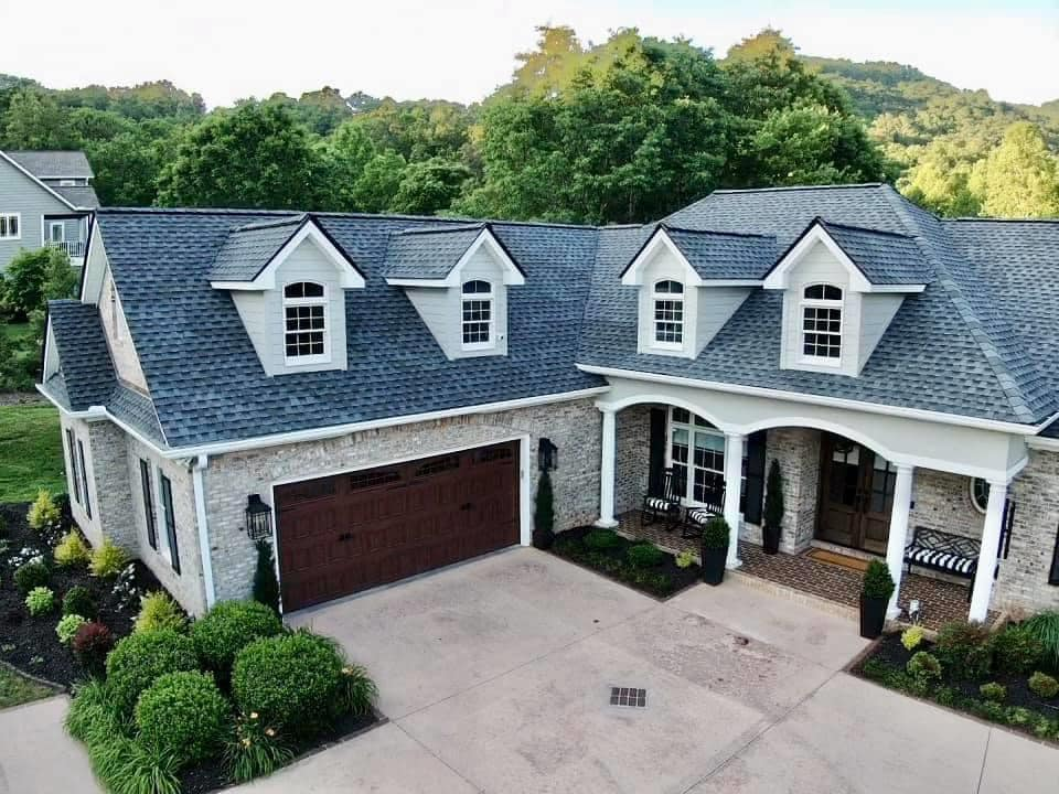 low aerial photo of the front of the home showing the details of the four front facing dormers over the entrance and attached garage area of the home.
