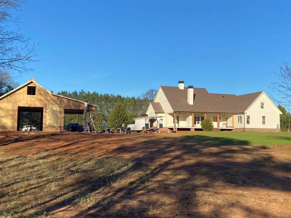 wide view of property of custom outbuillding showing the residence and proximity to custom outbuilding under construction