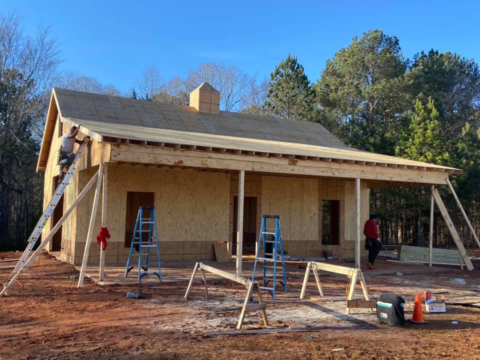 Custom outbuilding under construction with front porch-like carport area and workshop storage shed